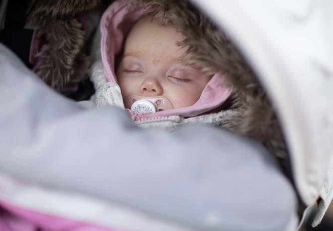 Bebis som suger på napp i barnvagn